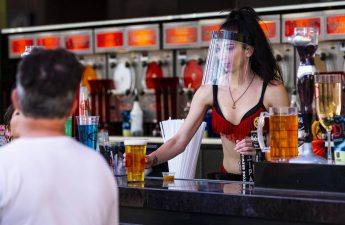 A bartender at the D Las Vegas wears a face shield while serving drinks at the Fremont Street E ...