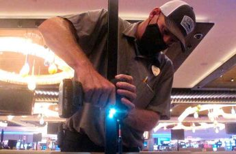 In this June 24, 2020 photo, Dean Loveland, a worker at the Hard Rock casino in Atlantic City N.J., installs plexiglass barriers between player positions at a card table at the casino a week before it was to reopen amid the coronavirus outbreak.