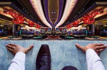 Pria Bisnis Berlutut di Garis Awal Dengan Latar Belakang Kasino